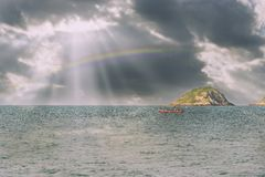 Fisherman boats out fishing on rainbow background. Fisherman boats out fishing in the sea on rainbow background Royalty Free Stock Images