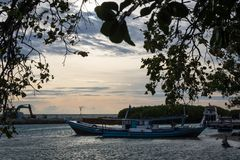 Fisherman boats on the small docks with beautiful sunset sky and silhouette leaves framing the scene. At Harapan Island, Indonesia royalty free stock images