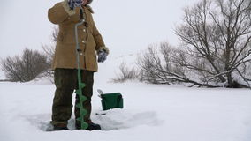 Fisherman, bore hole on the snow-covered lake in search of a good fishing place. stock footage