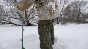 Fisherman, bore hole on the snow-covered lake in search of a good fishing place. stock video footage