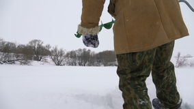 Fisherman, bore hole on the snow-covered lake in search of a good fishing place. stock video
