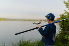 A fisherman boy on the river bank with a fishing rod in his hand Stock Images