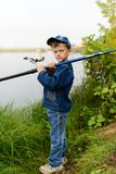 A fisherman boy on the river bank with a fishing rod in his hand Royalty Free Stock Photo