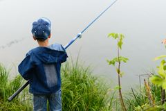 A fisherman boy on the river bank with a fishing rod in his hand Stock Image