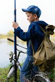 A fisherman boy on the river bank with a fishing rod in his hand. A child on a bicycle with a backpack on the shore of the river with fishing accessories.It Stock Photo