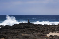Fisherman braves big waves at Kealakio Bay,. Southern most point in USA Royalty Free Stock Photography