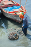 Fisherman bring mussels in the net soak the water royalty free stock photography