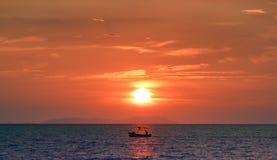 Fisherman on calm sea at sunset. Royalty Free Stock Image