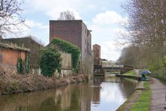 Fisherman on canalside path, old industrial buildings, Stoke-on-Trent Royalty Free Stock Image