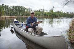 Fisherman in a canoe on a lake shows a walleye Royalty Free Stock Photos