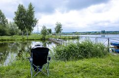 A fisherman in a cap sits in a chair near the lake with a fishing rod and catches fish. Meditation river activity angling hobby leisure recreation summer royalty free stock image