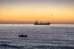 Fisherman and cargo ship sailing in the sea on sunrise Royalty Free Stock Photos