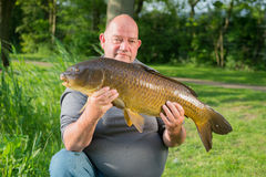 Fisherman with carp Stock Photography