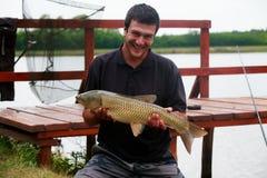 Fisherman and carp Royalty Free Stock Photo