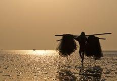 Fisherman carrying fishing net. Stock Photos