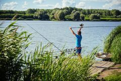 Fisherman cast fishing rod in lake or river water. Man fish with spinning tackle on wooden pier. Adventure, sport, activity. Spin fishing, angling, catching royalty free stock image