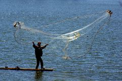 Fisherman cast net fishing in Indonesia. Fisherman throwing fishing net from a small wooden boat into the sea in Indonesia Royalty Free Stock Photo