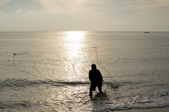The fisherman cast a net the se. A in the morning, at sunrise, Songkhla province, Thailand country stock photography
