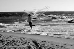 Man with cast net on the beach Florida, USA. Fisherman with cast net trying to catch bait fish on the ocean surf stock photos