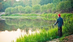 Fisherman Casting on Calm River Royalty Free Stock Image