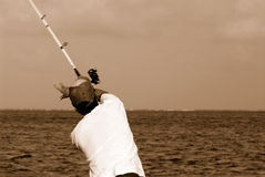 Fisherman casting line. Sepia rear view of fisherman casting rod and line, sea in background Royalty Free Stock Images