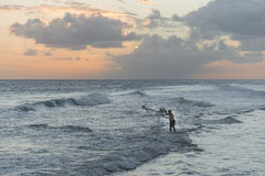 Fisherman casting net in Barbados Stock Photo
