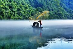 The Fisherman casting a net. In the early morning, the mist still coversed the river. A fisherman started to cast his first net royalty free stock photos