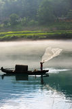 Fisherman casting net on river. A fisherman casting his net from the boat on the river royalty free stock images