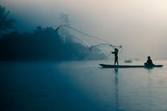 Fisherman casting out his fishing net early in the morning. Fisherman casting out his fishing net in the river by throwing it high up into the air early in the Royalty Free Stock Photos