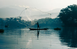 Fisherman casting out his fishing net in the river. Fisherman casting out his fishing net in the river by throwing it high up into the air early in the blue Stock Photography