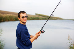Fisherman casting rod. Fisherman casting spinning rod in a freshwater lake Royalty Free Stock Image