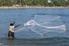 A fisherman casts his net into the sea at Arugam Bay on Sri Lanka's east coast. Stock Photography