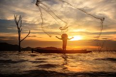 Fisherman catch fish by his fishing net. Fisherman catch fish by his fishing net during sunset stock images