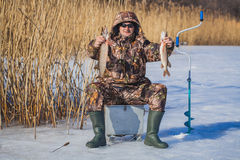 Fisherman catch pike on winter fishing Stock Photography