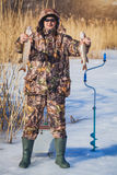 Fisherman catch pike on winter fishing Royalty Free Stock Photos