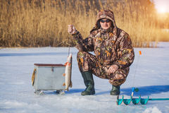 Fisherman catch pike on winter fishing Royalty Free Stock Photo