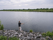 Fisherman catches fish. Concept of rural getaway. Fisherman with fishing rod on the river bank catches fish. Fishing, spinning reel, fish, river. Concept of Royalty Free Stock Photos