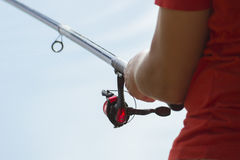 Fisherman catches a fish. Hands of a fisherman with a spinning rod in hand closeup. Spin fishing reel.  Stock Photos