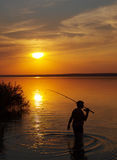 Fisherman catches fish on the lake at sunset. Fisherman catches fish by spinning on the lake at sunset stock photos