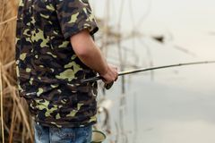 Fisherman catches fish by the river. Man holds fishing pole stock photo