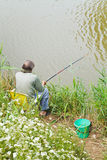 Fisherman catches a fish from riverbank Royalty Free Stock Photo