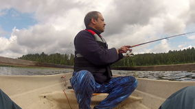 Fisherman catches a fish on rowing boat stock footage