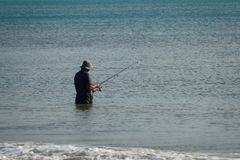 The fisherman catches fish in the sea on a fishing pole standing in water royalty free stock images