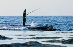 Fisherman catches a fish in the sea Stock Image