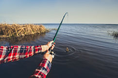 fisherman catches fish on the shore of the lake, holds his hands spinning against the beautiful lake Royalty Free Stock Photo