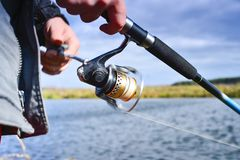 A fisherman catches a fish. Spinning reel closeup. Shallow depth of field on the spool of fishing line stock photography