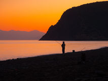 Fisherman catches a fish at sunset Royalty Free Stock Photography