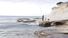 Fisherman on a white rock catches fish. A fisherman catches fish on white skies on a cloudy day stock video
