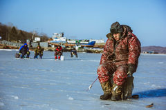 Fisherman catches fish in the winter Russia Vladivostok Russian island 22.12.2013 Royalty Free Stock Photos