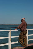 Fisherman catches from the pier. Elderly fisherman catches from the pier in the afternoon Royalty Free Stock Photography
